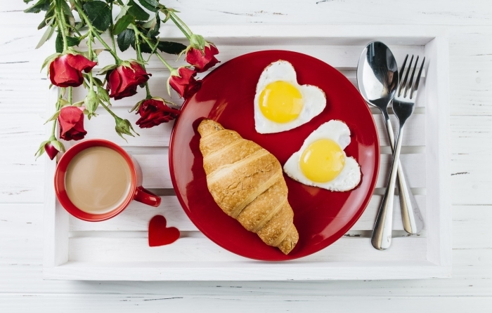 bouquet de roses rouges meilleur petit déjeuner assiette ronde rouge croissants oeufs en coeur