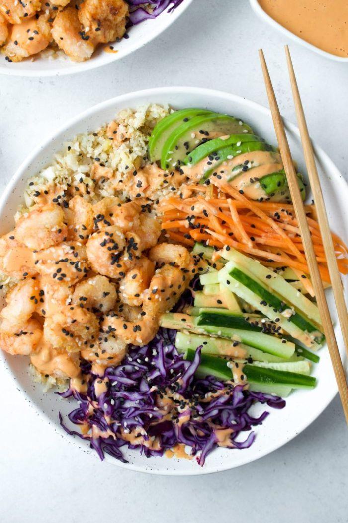 bowl healthy avec crevettes grillées avec chapelure concombres chou graines de sésame noir avocat sauce poke bowl