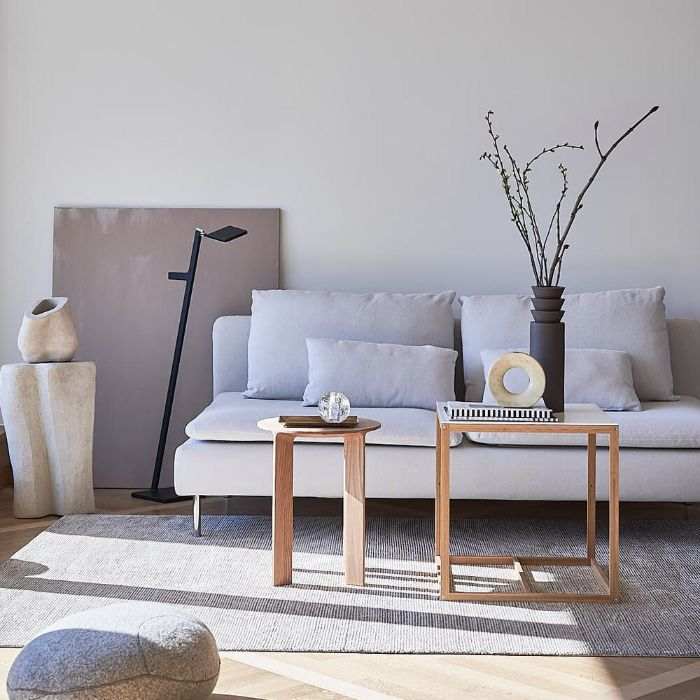 canapé blanc tables basses minimalistes de bois tapis gris vase gris anthracite murs blancs tableau gris