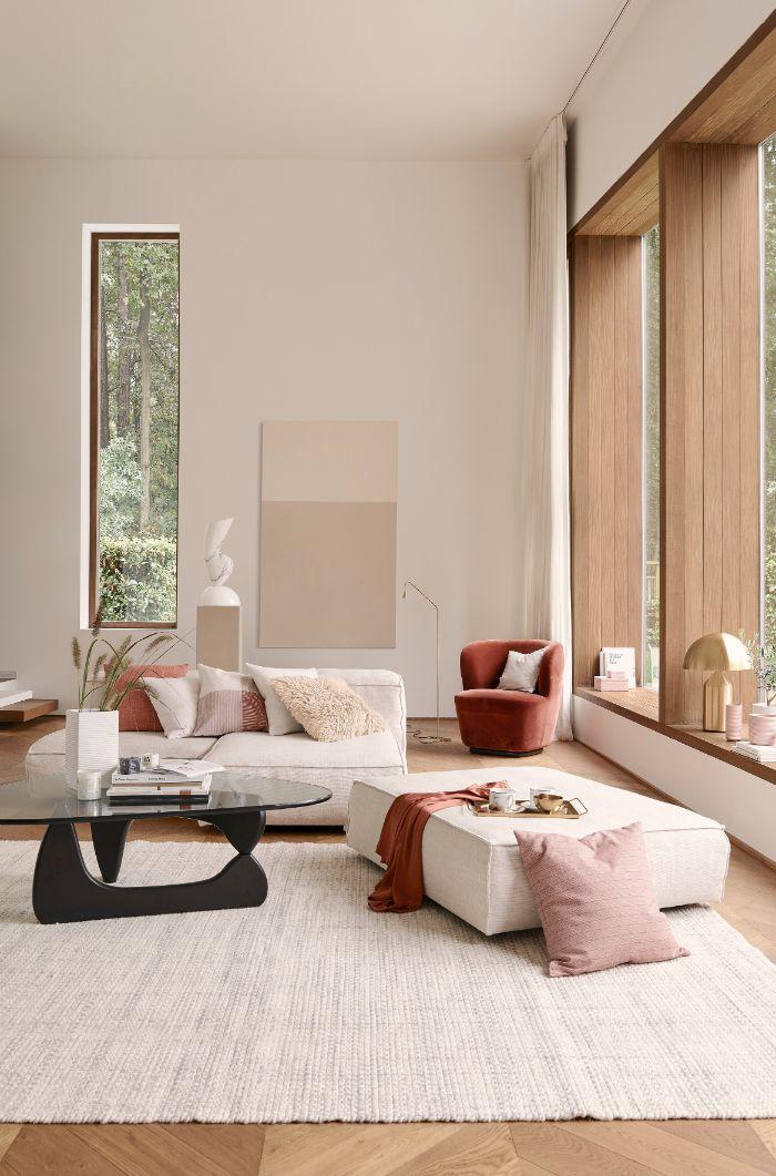 canapé et table matelassé blanc table bois et verre fauteuil couleur cuivre tapis blanc maison style japonais deco salon chic épuré