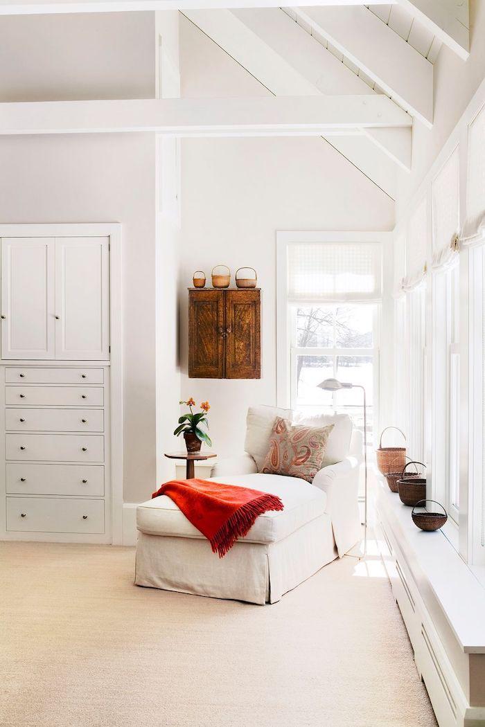 canapé tendance 2021 une chambre blanche avec des tissus naturels en cotton et un placerd au mur en style rustique