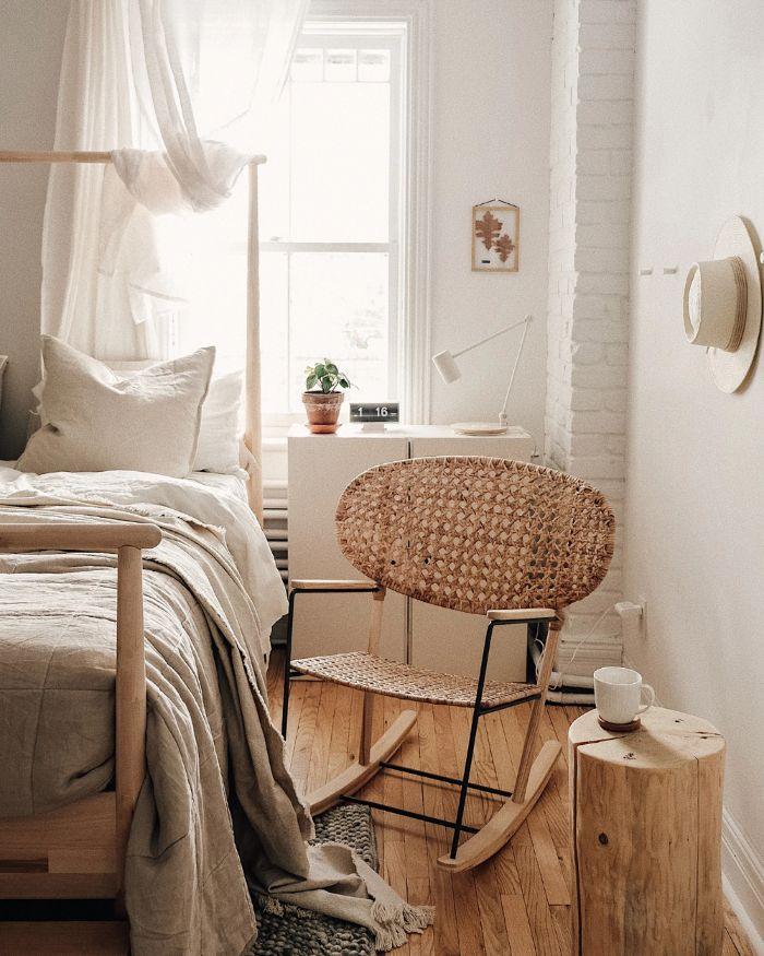 chaise à bascule tressé parquet bois clair murs peinture blanche chambree table tronc linge de lit gris sur lit bois deco chambre zen