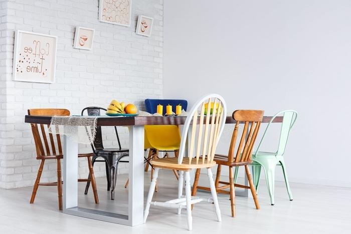 chaise colorée salle à manger table manger bois et blanc cadre mur briques blanches bougies jaunes