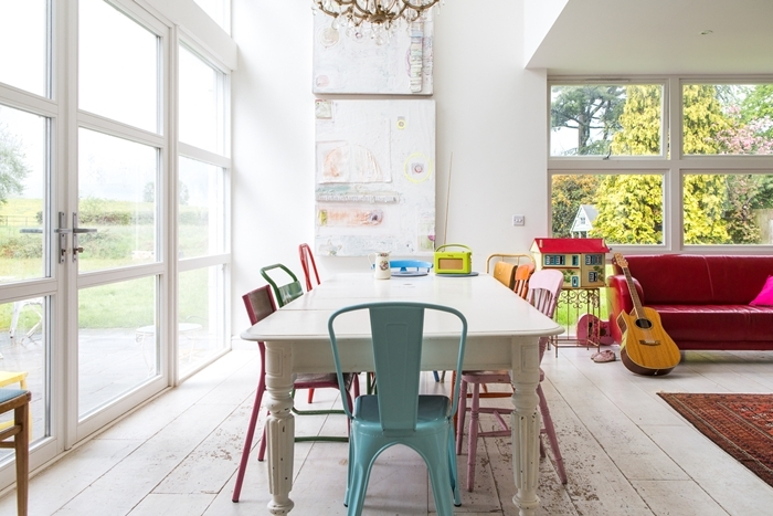 chaises colorées dans salle à manger table bois blanc design intérieur accents pops canapé rose fuschia