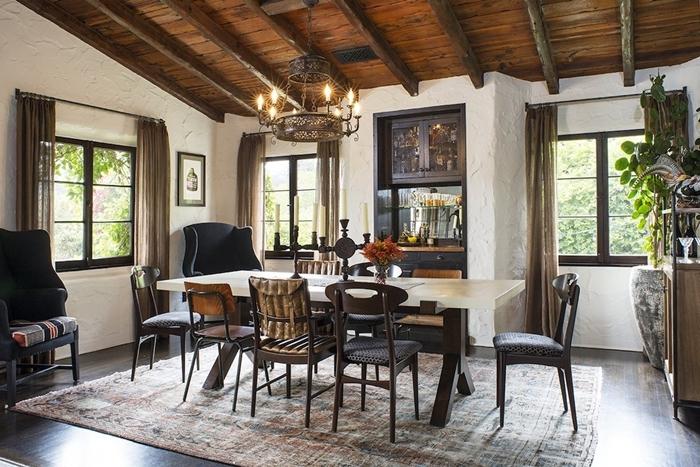 chaises dépareillées salle à manger plafond bois foncé poutres apparentes table bois foncé chaise marron
