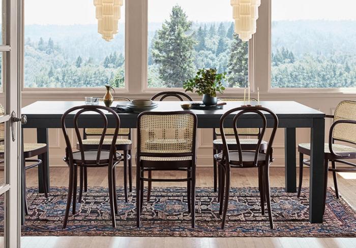 chaises dépareillées salle à manger table bois gris anthracite tapis foncé motifs ethniques fenêtres