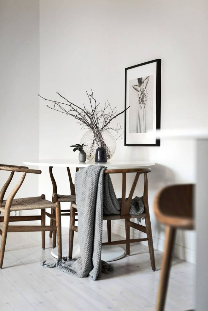 chaises de bois autour d une table blanche murs blancs parquet bois blanchi portrait photo femme en robe