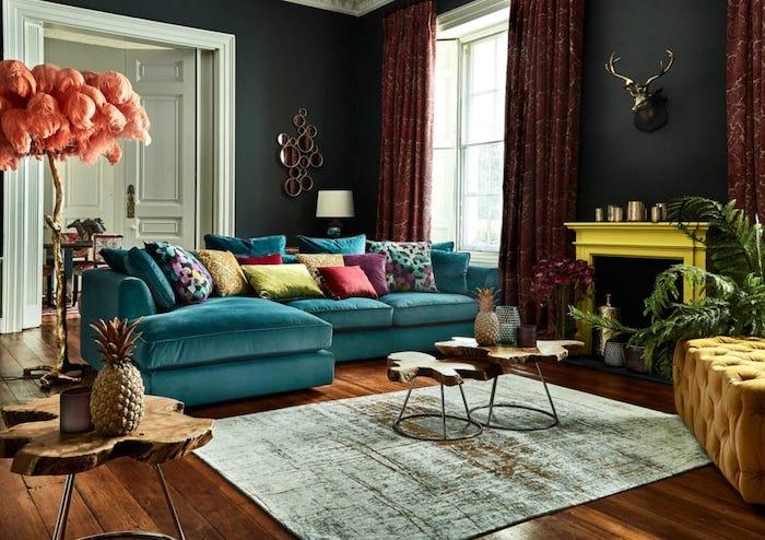 chambre adulte 2021 avec un canapé turquois et des nombreux coussins multicolores avec une cheminée en jaune lumineux