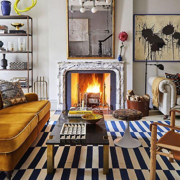 chambre tendance 2021 une cheminée allumée et un tapis à rayures en bleu marine et blanc avec un canapé jaune