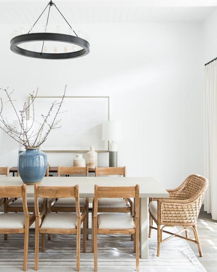 chandelier métal noirci bougies chaises dépareillées salle à manger table manger bois blanc vase bleu