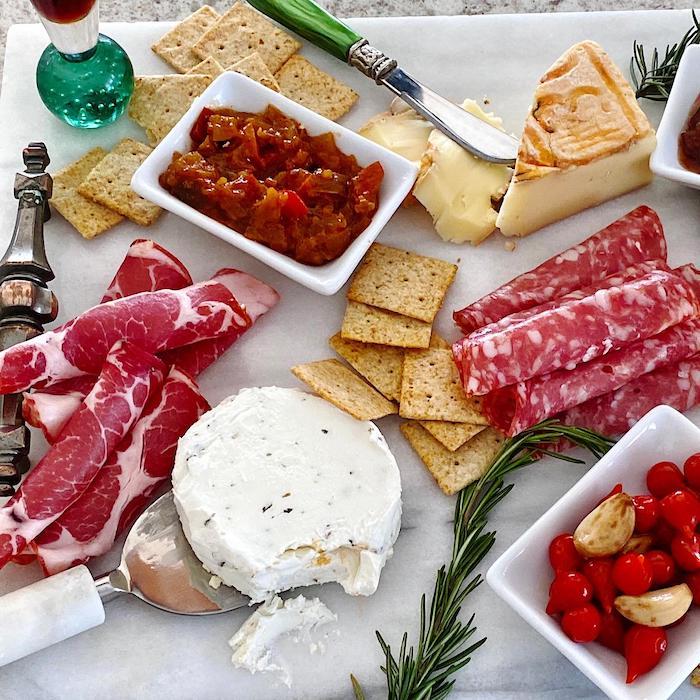 charcuterie raclette avec des salami des craquelins et de l ail sur une assiette blanche garni avec de romarin