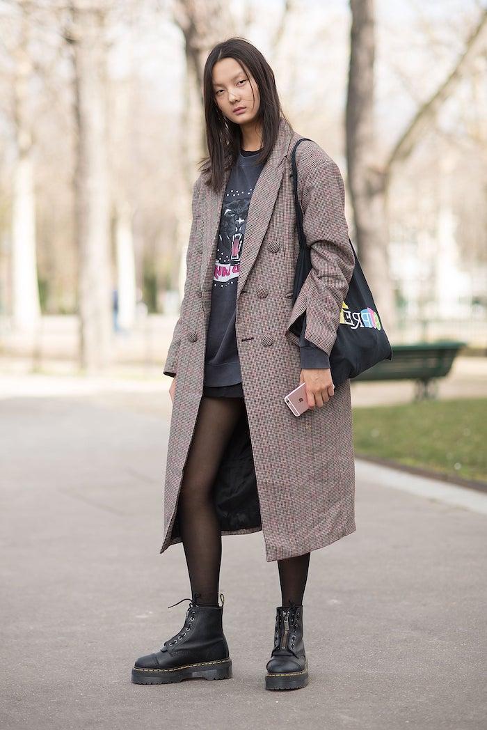 chaussure style doc martens avec un collant noir manteau ample et short noir