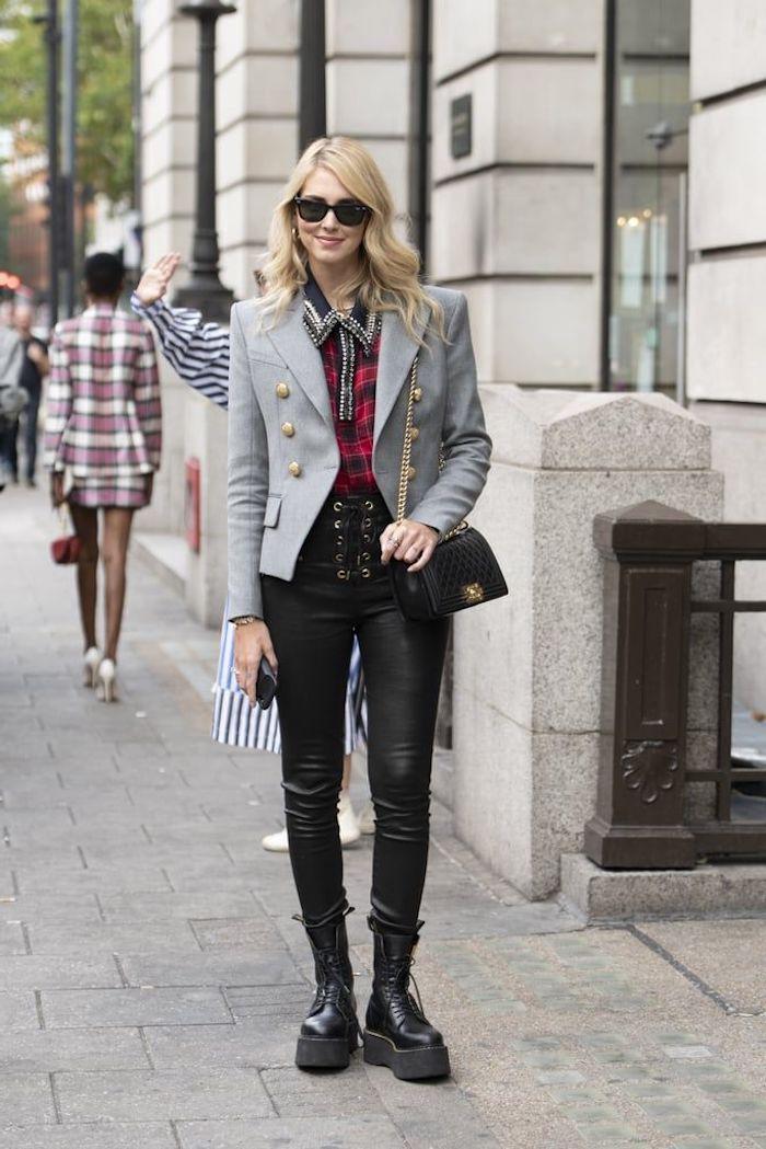 chaussures doc martens combinées avec un pantalon noir en cuir blazer gris et un chemisier a carreaux