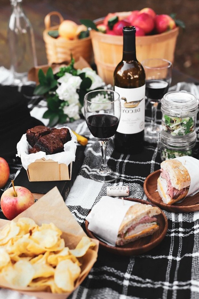 comment celebrer saint valentin a la maison une nappe a carreaux avc deux sandwichs une boutelle de vin et des chips