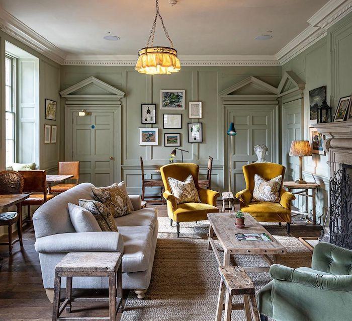 couleur peinture salon tendance 2021 vert olive sur les murs et deux fauteuils en jaune avec une table rustique