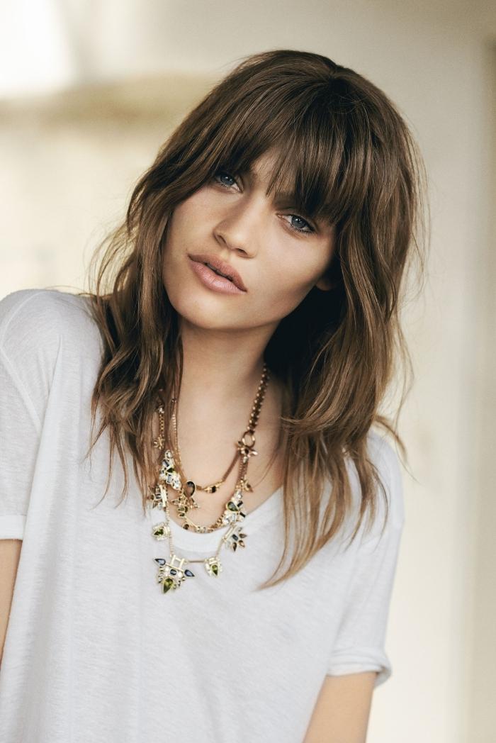 coupe cheveux mi long dégradé avec frange t shirt blanc collier motifs floraux yeux bleus