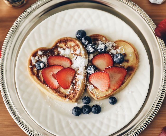 crepes américaines en forme de coeur garnis de fraises et de sucre surprise saint valentin petit dej
