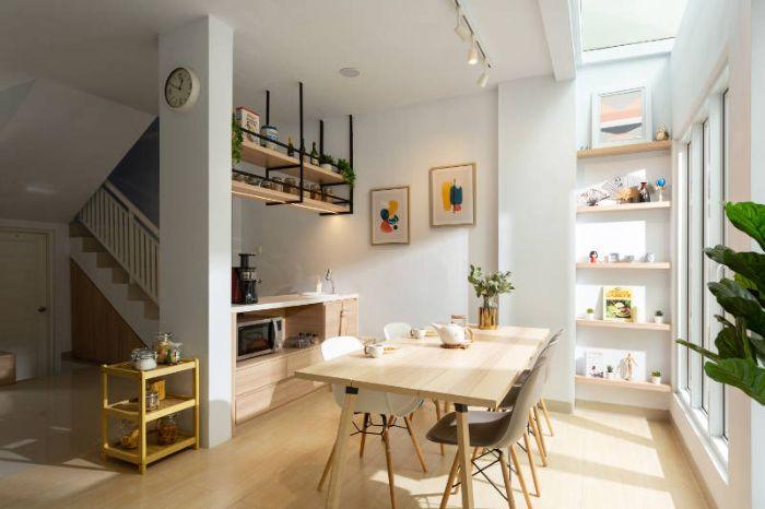 cuisinette de bois ouverte sur salle à manger bois et chaises scandinaves parquet bois clair murs blancs décorés d art
