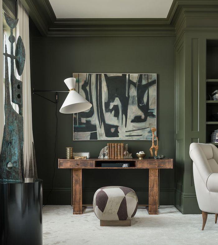 déco murale tendance des murs en vert olive une tabourette devant une table rustique et un tableau abstrait