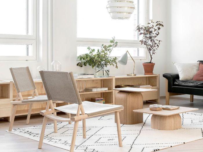 deco japandi interieur minimaliste avec chaises tables et meuble bas bois canapé cuir noir plantes suspension tapis blanc à la scandinave