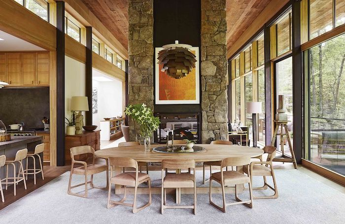 deco salle a manger tendance des meubles en style rustique des grandes feneters et un mur en pierres sur un tapis beige