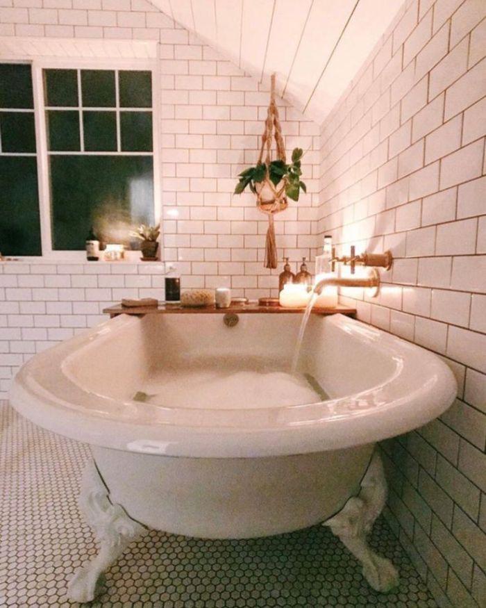deco salle de bain blanche avec baignoire blanche et plantes suspendues macramé robinetterie en laiton bougies