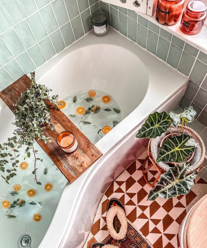 deco salle de bain cocooning avec baignoire blanche carrelage jaune moutarde et blanc pont de baignoire bain aux oranges laurier brins de pin plantes vertes d intérieur