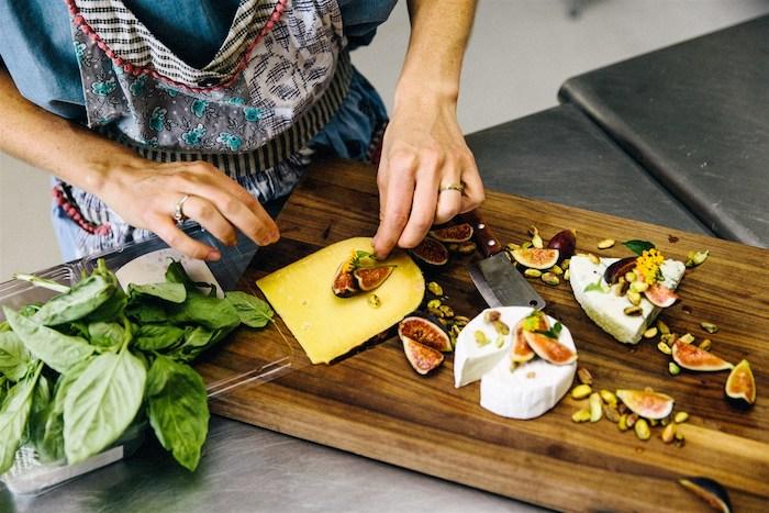 decoration plateau de charcuterie, une femme qui met sur un plateau des fromages des figues et des noix decorer avec basil