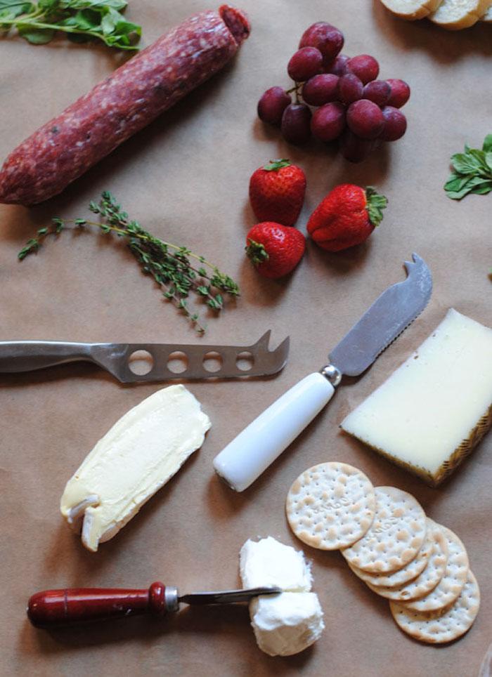 des couteaux de frommages et de beurre des fraises e raisins sur une table avec des herbes