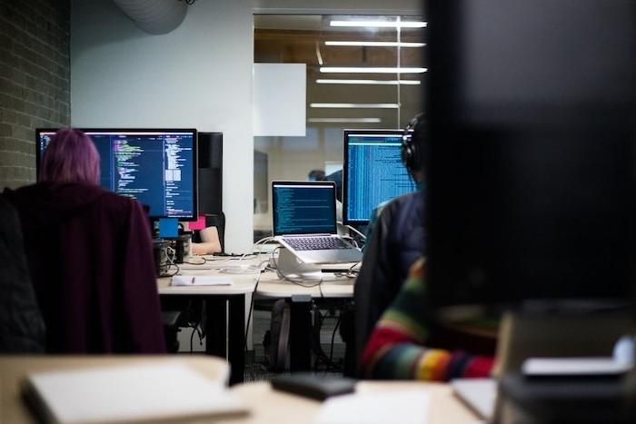 des employes qui travaillent dans un bureau avec des ordinateurs
