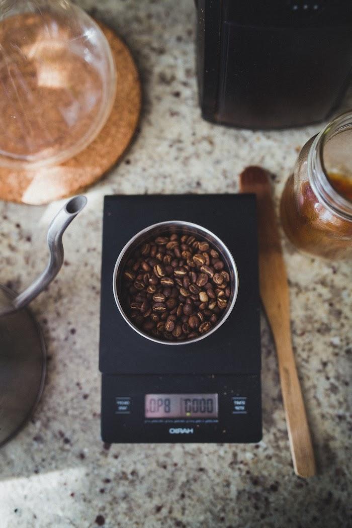 des graines de café sur une balance placé au comptoir en marbre