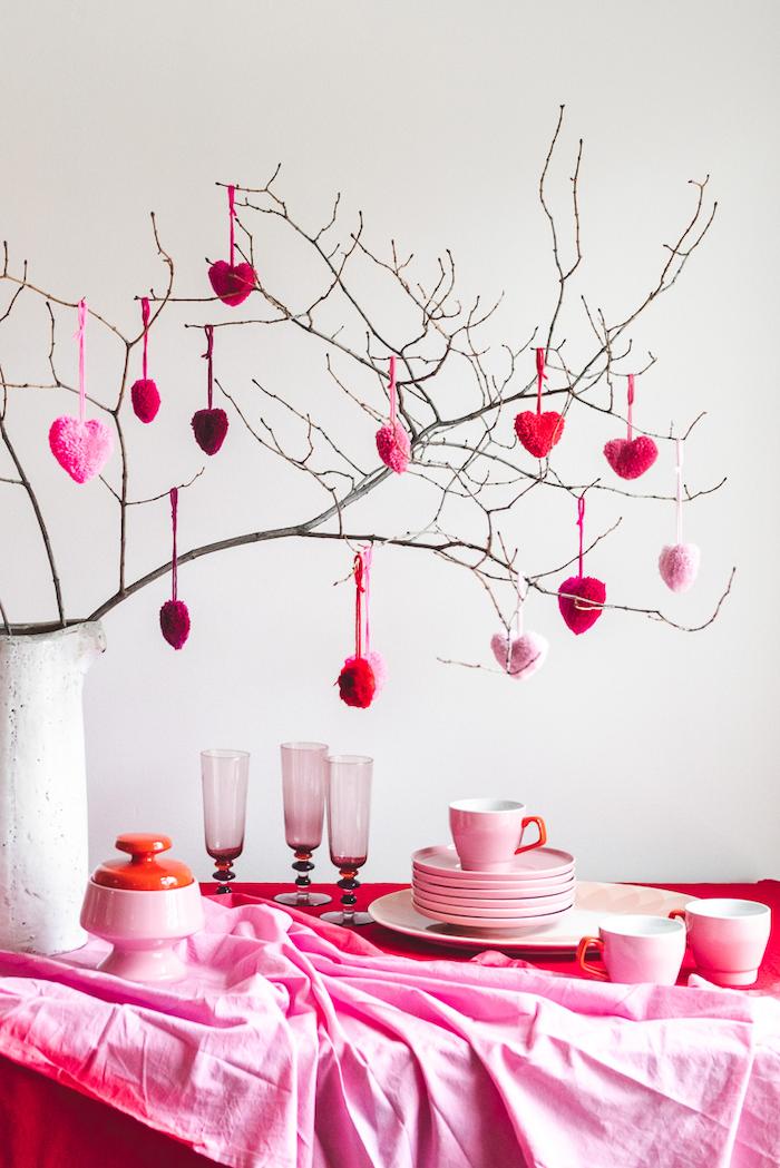 des petites coeurs décoratifs susprendus d une branche une table a nappe rose avec des couverts et des assiettes jpg