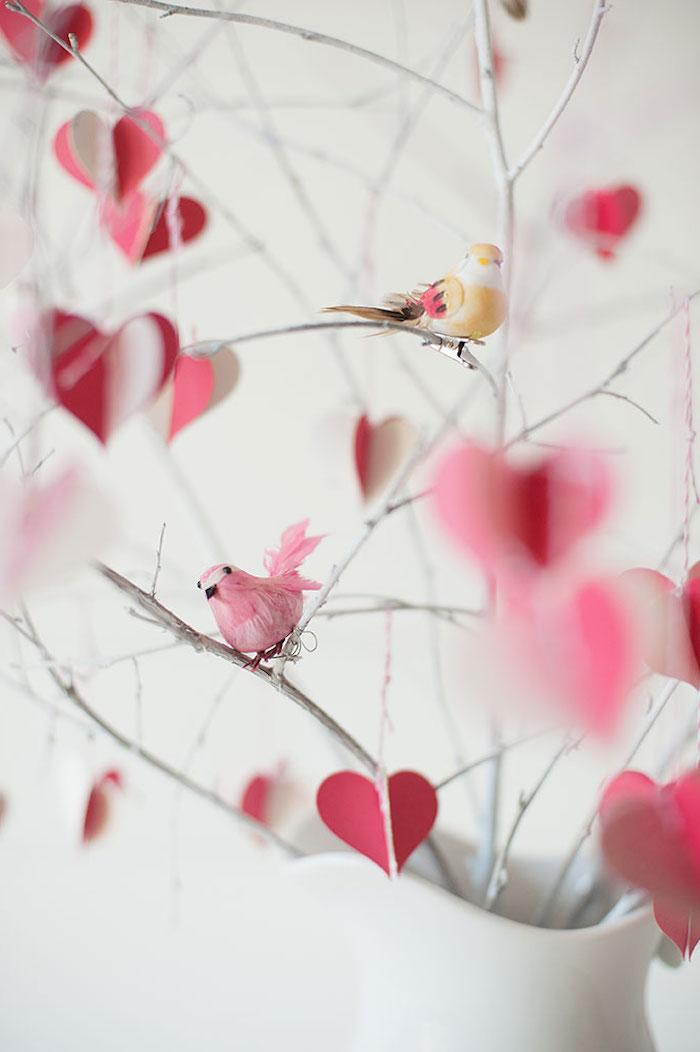 des petits oiseaux décoratifs penchée sur des branches dans une vase décoration saint valentin