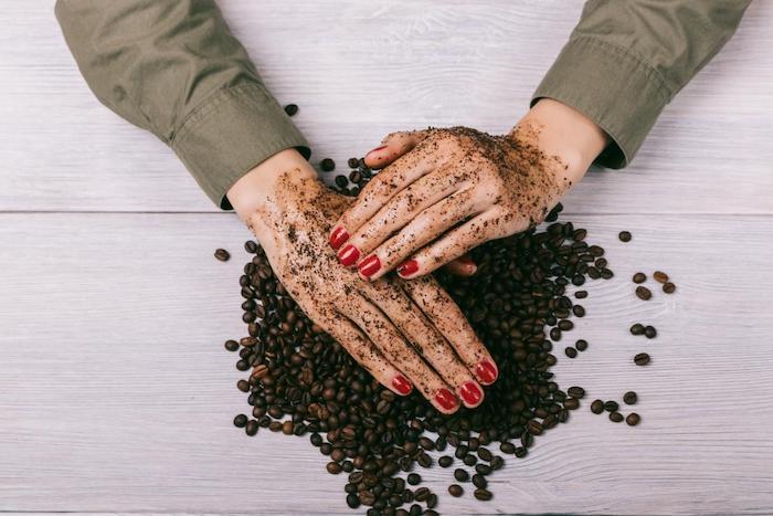 deux mains avec des ongles peints en raide qui frottent de l exfoliant de café