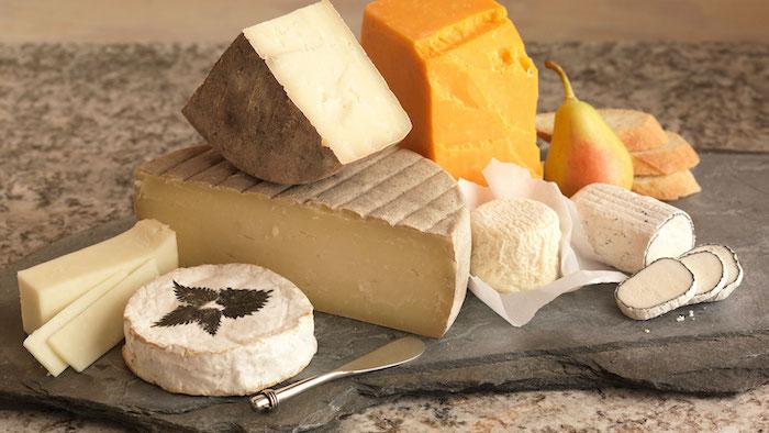 differentes types de frommages sur un plateau en pierre avec un couteau de beurre
