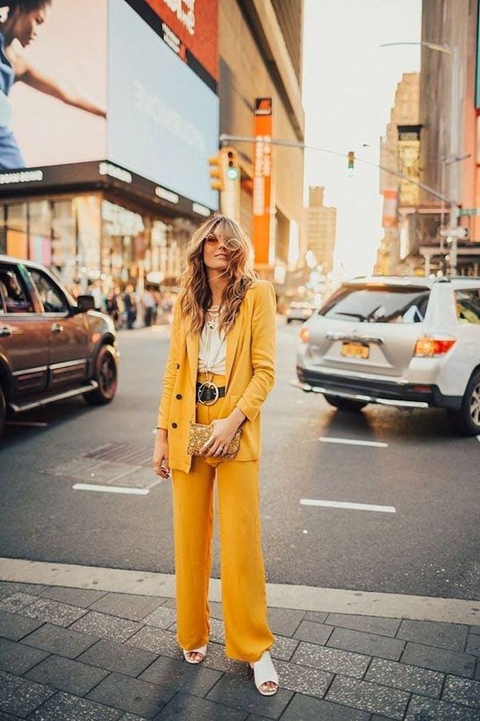 ensemble costume femme en jaune couleur pantone 2021 avec un ceinture au grand bouclier et des sandales blanc une femme dans un)grand boulevard