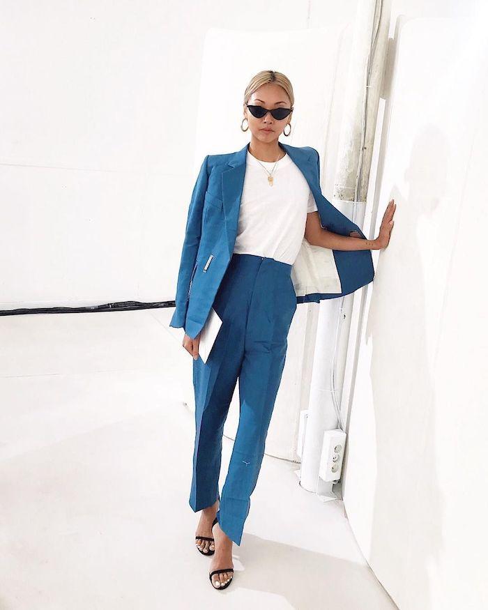 ensemble pantalon femme en couleur bleu vive avec un t shirt des sandales et bijoux dores dans un espace blache