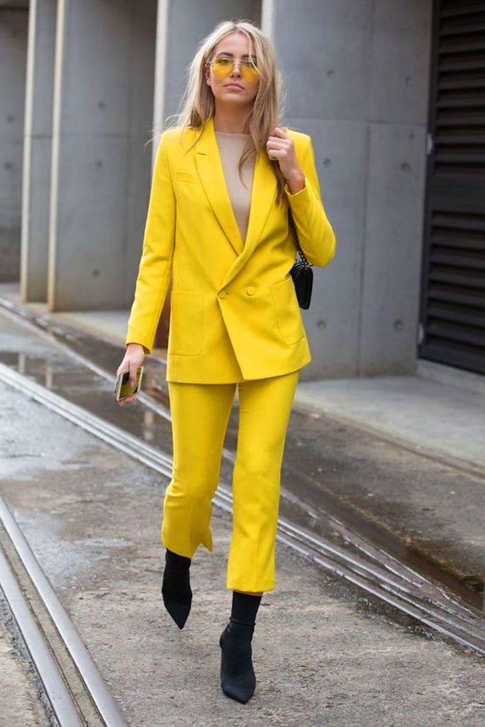 ensemble tailleur femme chic en couleur jaune illumineuse pantone 2021 des bottes noires et lunette tintes