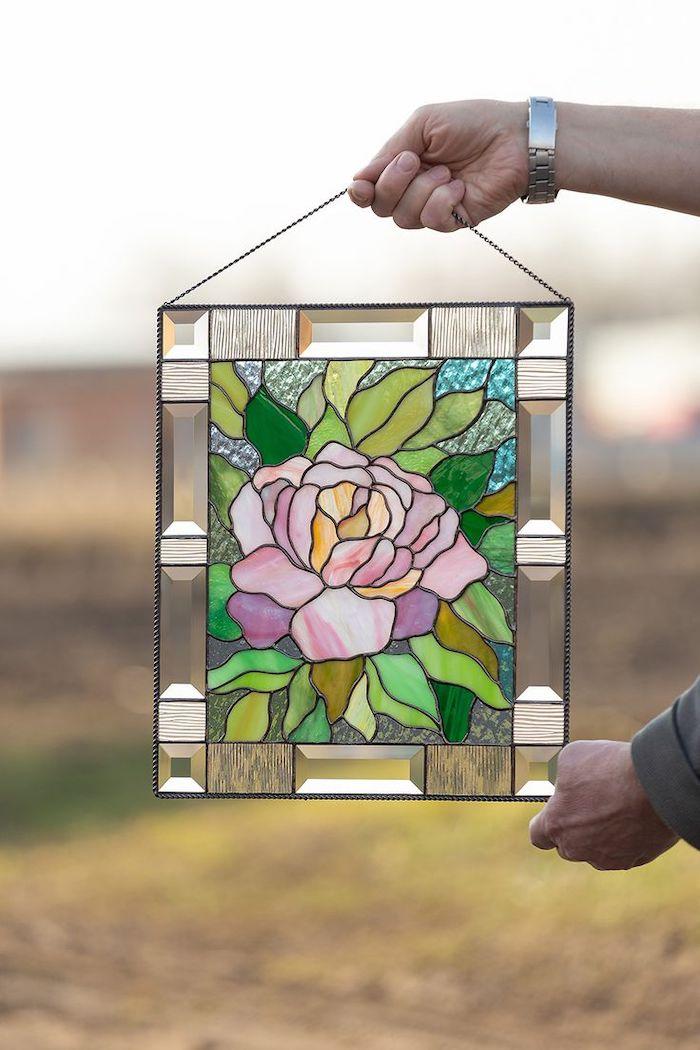 exemple ou idée d un oeuvre crée avec de la peinture sur verre deux mains qui la tiennetn