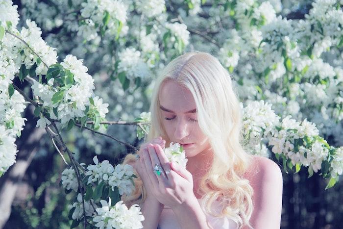 femme blonde photographe pres d un arbre flouri