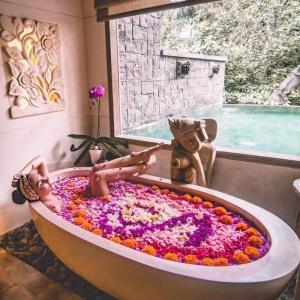 grande baignoire blanche remplie de pétales de fleurs avec vue sur l extérieur statuette de bouddha pierres d intérieur deco orientale cocooning
