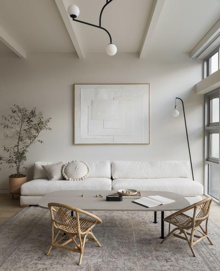 idée canapé blanc chaises tressés table basse grise murs blancs plafond haut tapis gris lampe suspension originale
