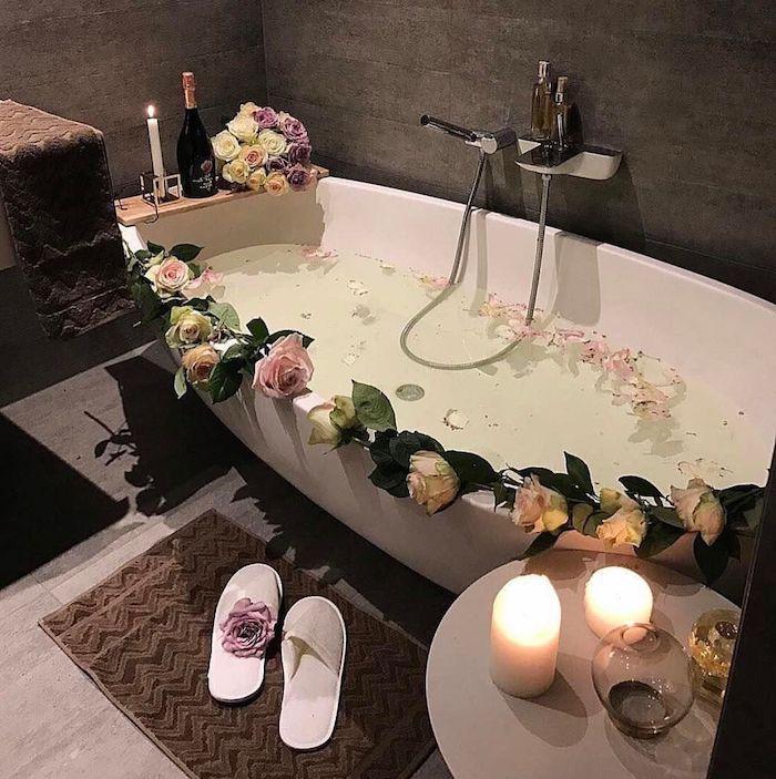 idée saint valentin une baignoire avec des fleurs deux bougies allumés sur une table basse