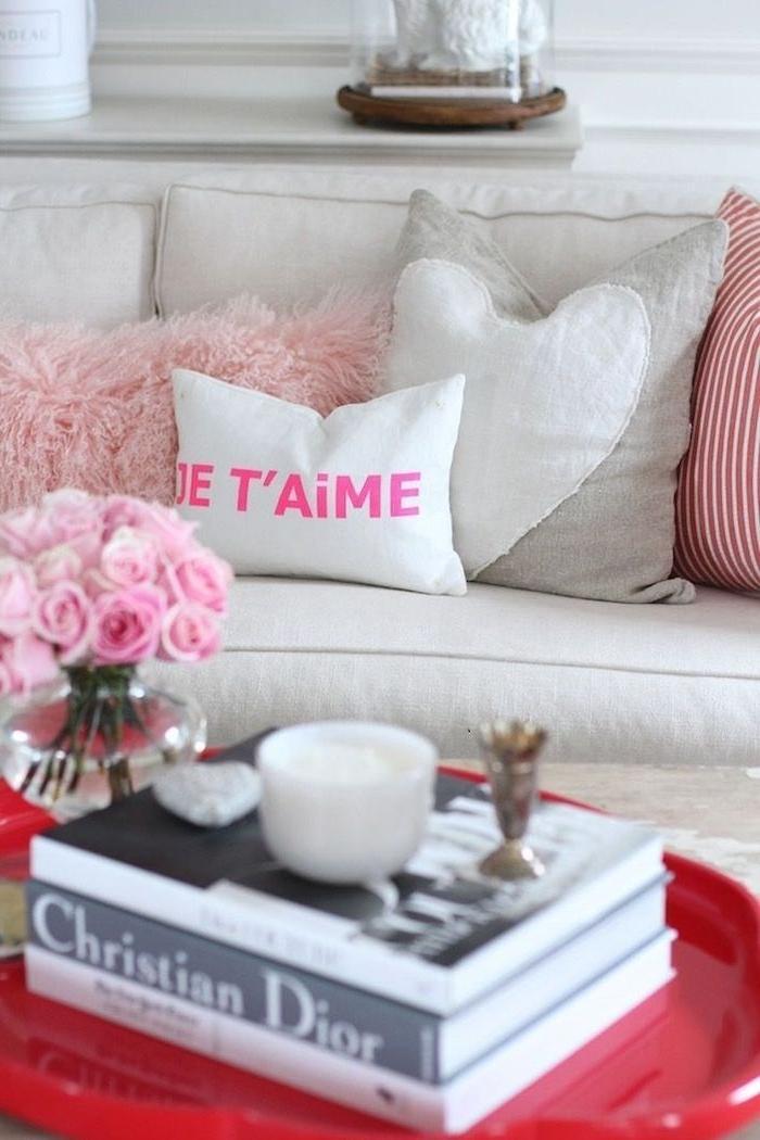 idée surprise saint valentin un canapé avec un coussin imprimé des livres sur une table rouge