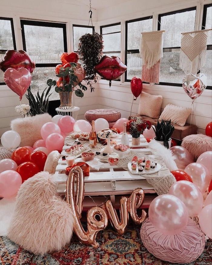 idée surprise saint valentin une salle de séjour décorée de ballons et des coussins roses