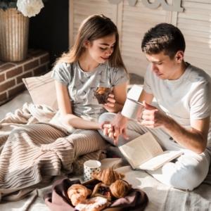 image couple romantique lit amour saint valentin croissants tasse café boisson chaude muffins mur briques