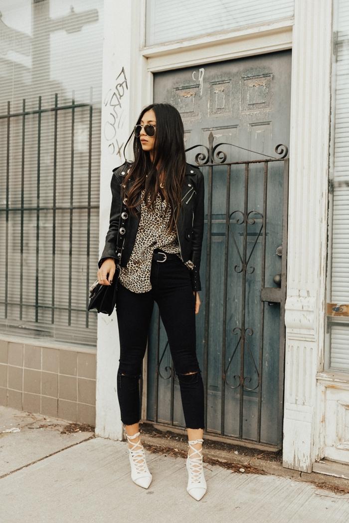 jeans noirs troués ceinture noire haut leopard chemise veste en cuir noir femme sac à main
