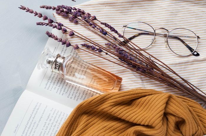 joli flacon de parfum en verre pose sur un livre ouvert lunette de vue hypi