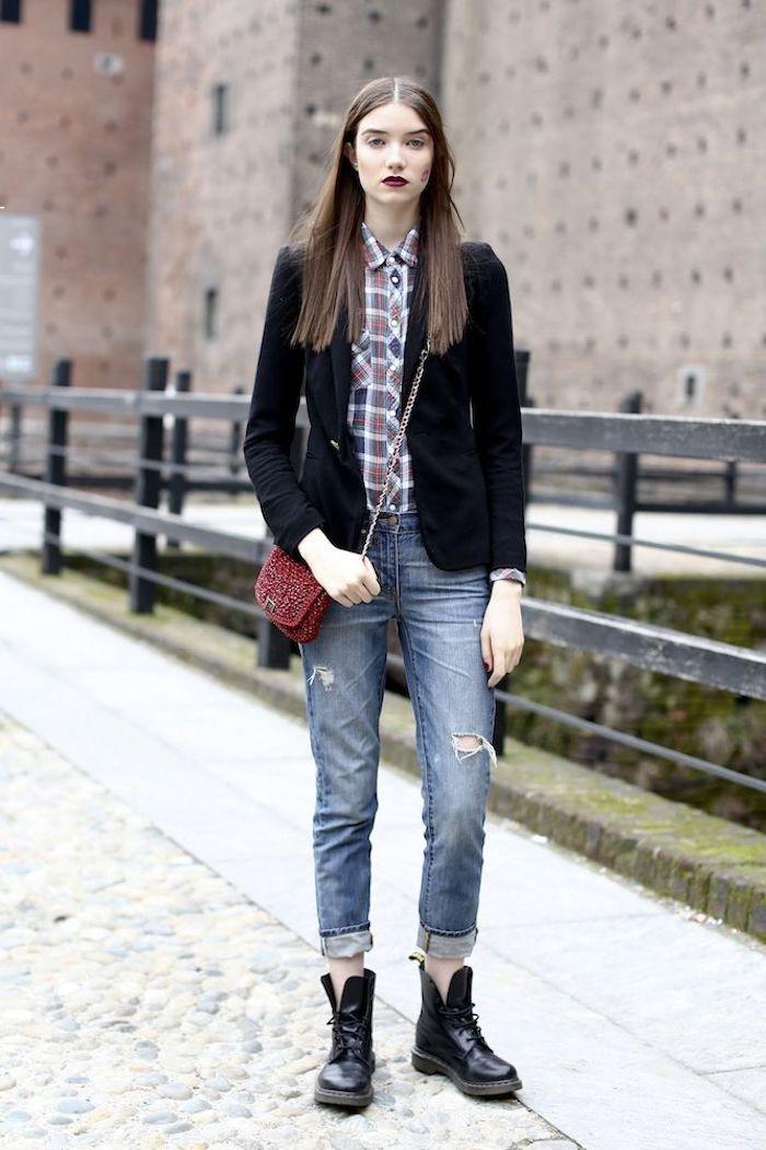 look avec doc martens une fille en jean déchiré blazer noir et sac en bandouliere rouge