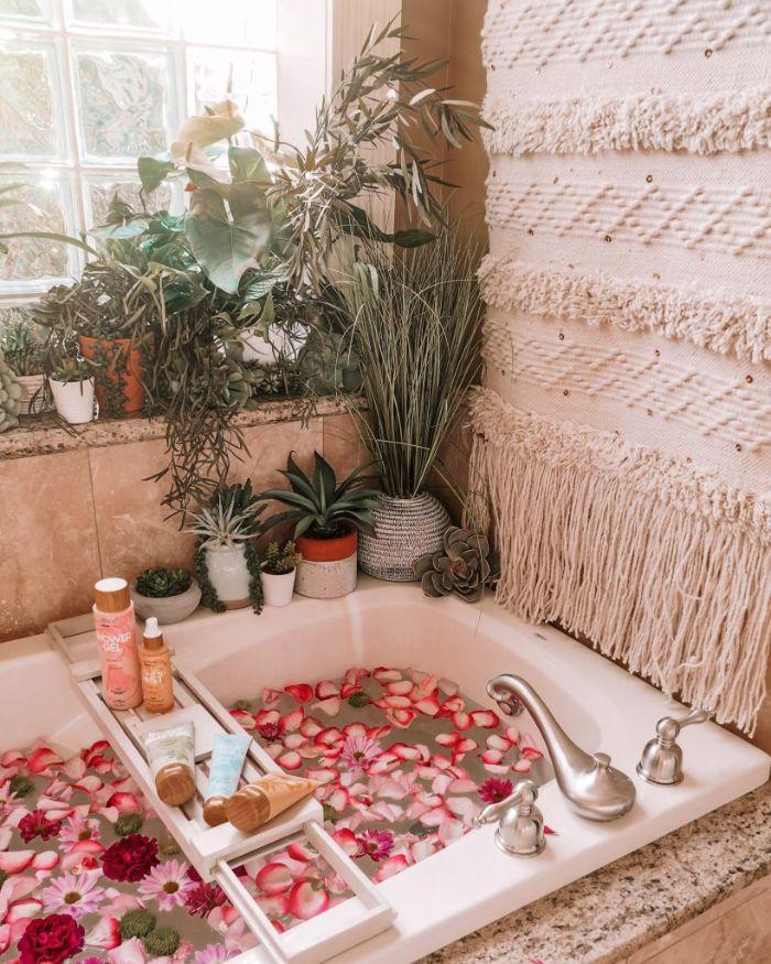 macramé murale dans salle de bain nature boheme chic avec baignoire blanche remplie de fleurs et pétales